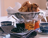Assorted Muffins in a Wire Basket with Assorted Jams and Jellies