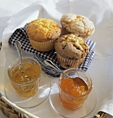 Assorted Muffins on a Blue and White Napkin with Apple Jelly and Apricot Jam