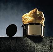 Popover-Brot in einem Topf auf Steinmauer, daneben ein Ei