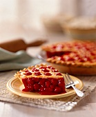 Cherry Pie Slice with Whole Pie in Background