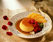 Orange caramel custard with raspberries and orange segments, on a plate