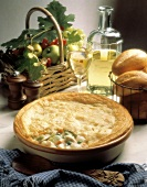 Chicken and vegetable pie in baking dish; wine, bread, fruit