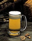Helles Bier im Glaskrug, daneben einige Erdnüsse
