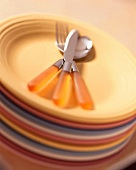Stack of Fiesta Plates with Orange Handled Flatware