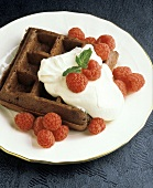 A chocolate waffle with raspberries and whipped cream
