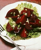 Beets quartered on lettuce with scallions