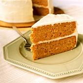 Ein Stück Möhrenkuchen mit weisser Glasur auf Teller