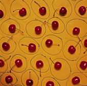 Einzelne frische Kirschen in Kreisen auf gelbem Untergrund