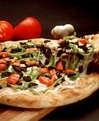 Gemüsepizza mit Paprika, Oliven & Käse, ein Stück angehoben