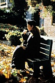 A Woman Sitting on a Bench Drinking Tea; Autumn