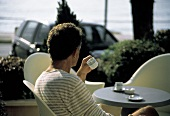 A Man Sitting at a Table Outside Drinking Espresso