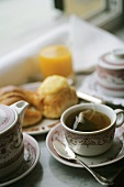 A Cup of Tea with the Tea Bag and Breakfast Rolls