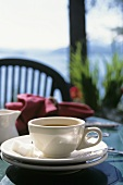 A Cup of Coffee and Saucer on an Outdoor Table
