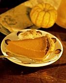 Stück Kürbispie mit Sahne auf Dessertteller (Pumpkin Pie)