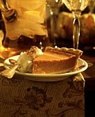 Ein Stück Kürbispie (Pumkin Pie) mit Sahne auf Dessertteller