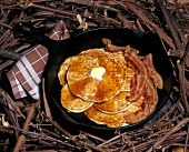 Pancakes with Maple Syrup and Butter in a Frying Pan; Bacon