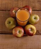Ein Glas trüber Apfelsaft umgeben von Äpfeln