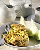 A Popover Filled with Scrambled Eggs and Chives; Melon Slices