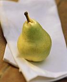 Eine grüne Birne auf weisser Stoffserviette