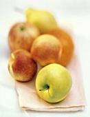 Ein Golden Delicious Apfel vor Obst (unscharf im Hintergrund)