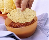 Hand Dipping Tortilla Chip into Salsa
