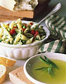 A Bowl of Pasta Salad with a Small Bowl of Dressing