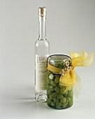 Eine Flasche Grappa & grüne Trauben im Glas als Geschenk