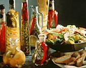 Kräuteröle und -essige neben Salat mit gegrilltem Hähnchen