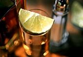 Ein Limettenschnitz auf einem Glas Tequila