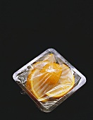 Orange Slices in a Platic Container with Plastic Wrap