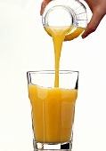 Orange Juice Pouring From a Bottle into a Glass