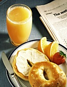 Bagel with Cream Cheese and Orange Juice; Newspaper