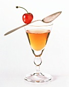 A Glass of Liqueur with a Spoon and Cherry