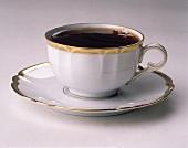 Schwarzer Kaffee in eleganter weisser Tasse mit Goldrand