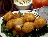 Frittierte Fischtaler auf Salatblättern und Pfannenwender