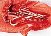 Assorted Candy Canes on Red Tissue Paper