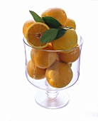 Many Oranges in a Tall Glass Bowl