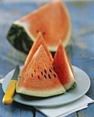 Wassermelonenschnitze mit Messer auf Dessertteller