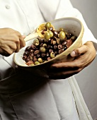 Chef Tossing Marinated Olives in a Bowl