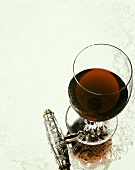 Glass of Red Wine with Silver Handled Corkscrew