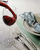 Pouring Red Wine into Glass; Place Setting