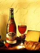 Eine Flasche Lambrusco neben Rotweinglas, Käse, Weissbrot