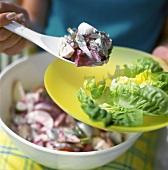 Heringssalat auf Teller anrichten