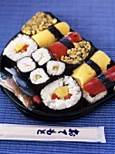 Sushi platter with soy sauce & ginger; chopsticks in packet