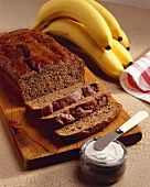 A Partially Sliced Loaf of Banana Bread; Cream Cheese