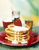 A Stack of Oatmeal Pancakes with Yogurt Sauce and a Strawberry