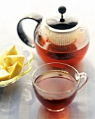Tea in glass cup and pot and wedge of lemon