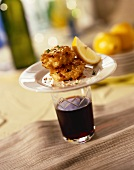Sesame Crab Cake Tapas on a Glass of Red Wine