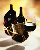 Bottles of Wine in Gift Bags with a Glass of Red Wine