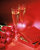 Two Flutes of Champagne, Roses and Candy on a Red Background
